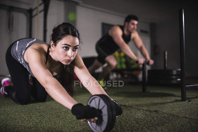 Crossfit training and fitness wheel pushups in gym — Stock Photo