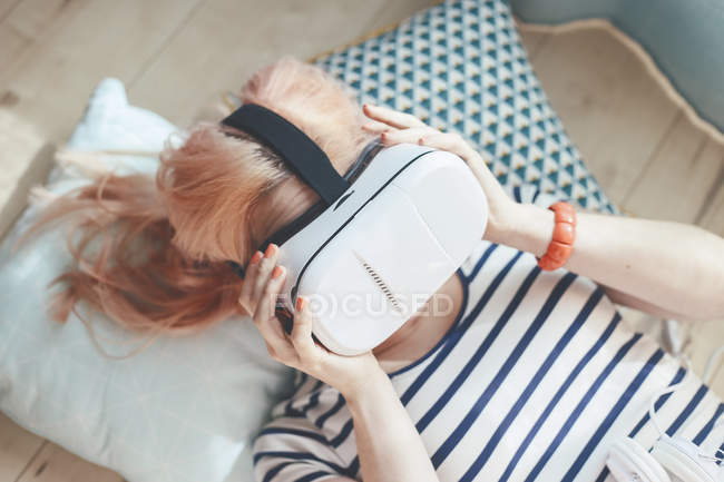 Young woman putting on Virtual Reality Glasses — Stock Photo