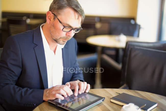 Businessman sitting in coffee shop — Stock Photo