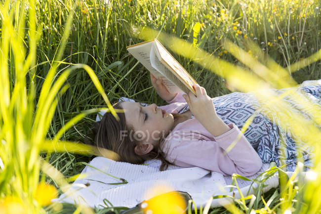Little girl lying on field of flowers reading a book — Stock Photo