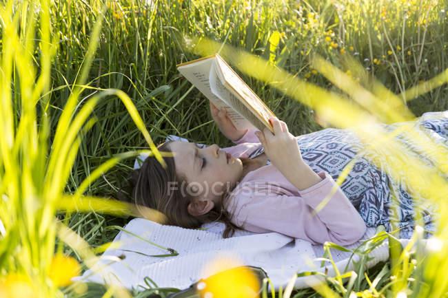 Маленькая девочка лежит на поле цветов и читает книгу — стоковое фото
