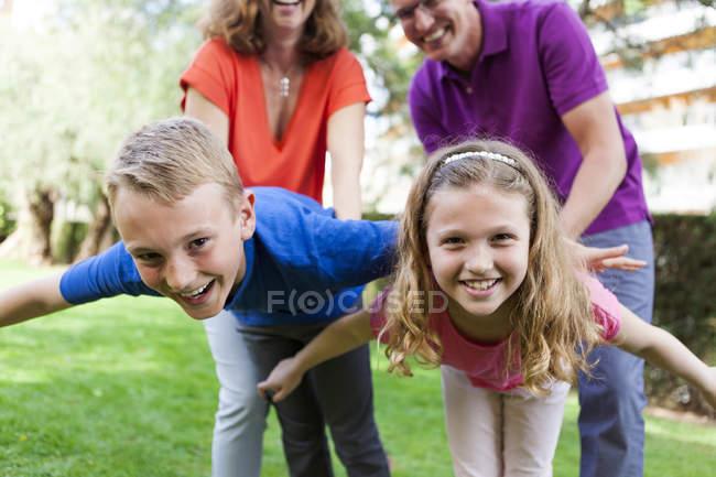 Ritratto del fratello e sorella che giocano con i genitori in giardino — Foto stock