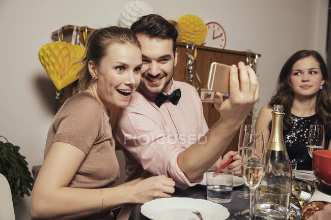 Friends taking selfies with smart phone on New Year's Eve — Stock Photo