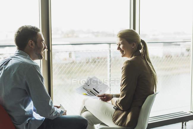 Zwei glückliche Kollegen am Fenster sitzen — Stockfoto
