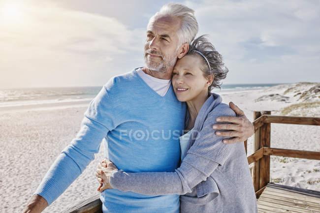 Glückliches Paar umarmen einander am Strand — Stockfoto