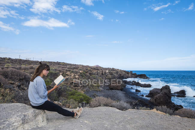 Young woman reading book at the sea — Stock Photo