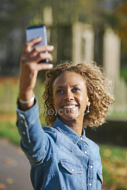 Porträt von lächelnden Frau nehmen Selfie mit smartphone — Stockfoto