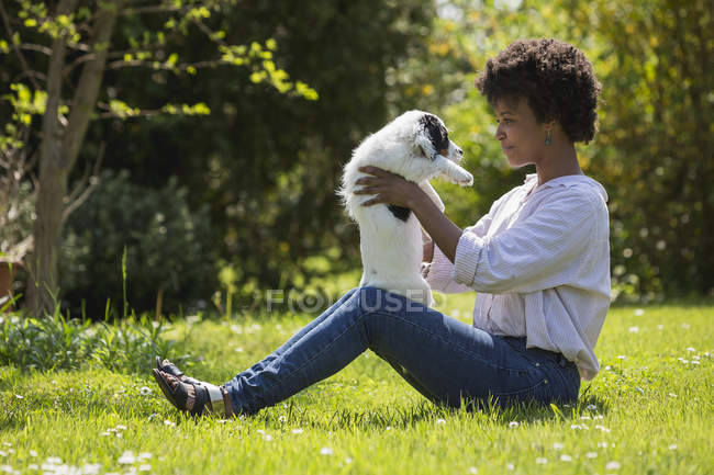 Woman sitting on meadow and playing with dog — Stock Photo