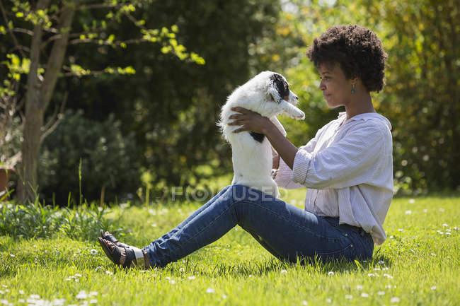 Femme assise sur la prairie et jouant avec le chien — Photo de stock