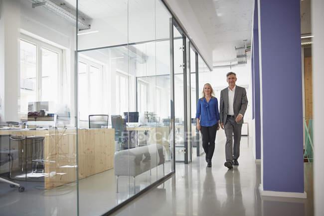 Бизнесмен и женщина идут по офисному коридору — стоковое фото