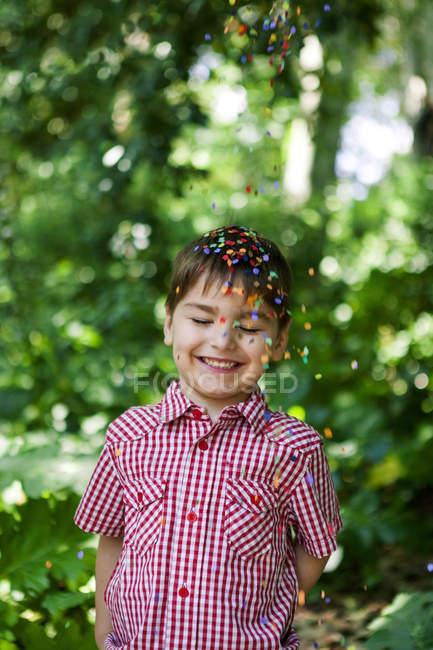Confetes caindo no menino feliz — Fotografia de Stock