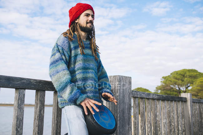 Young man with dreadlocks and wool cap playing a drum — Stock Photo