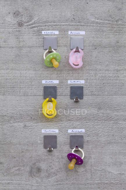 Schnuller hängen Betonwand mit namens-tags — Stockfoto