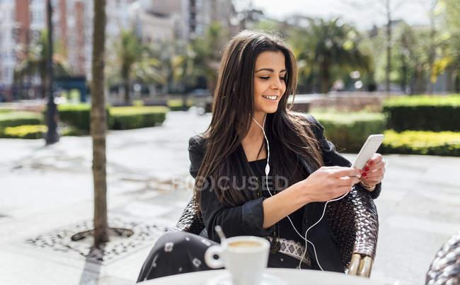 Bella giovane donna che prende un caffè, caffè pavimentazione con smartphone, ascoltare musica — Foto stock