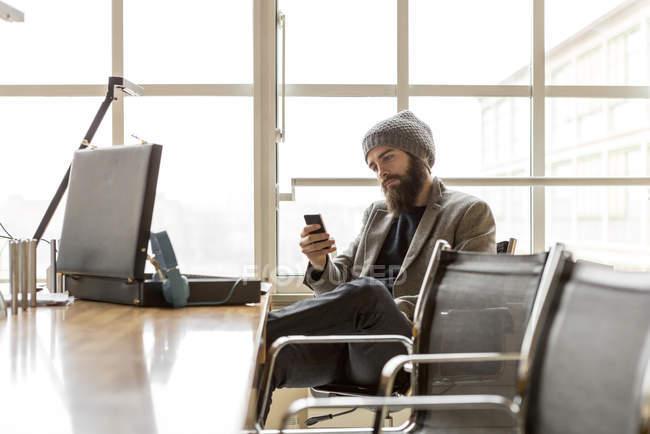 Jovem empresário vestindo chapéu gorro usando smartphone no escritório — Fotografia de Stock