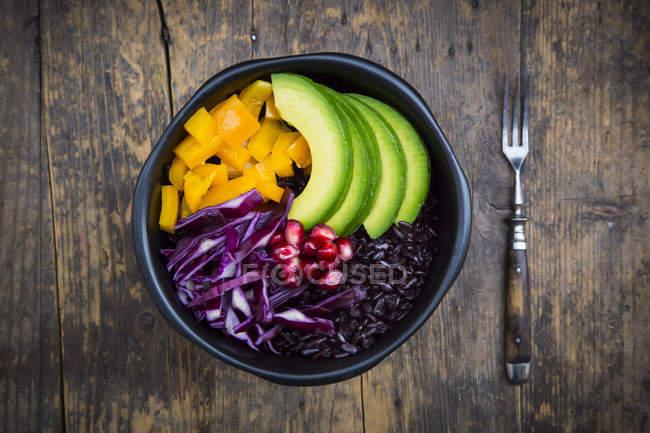 Обід миску з чорний рис, авокадо, жовтий перець, Червона капуста і граната по дереву — стокове фото