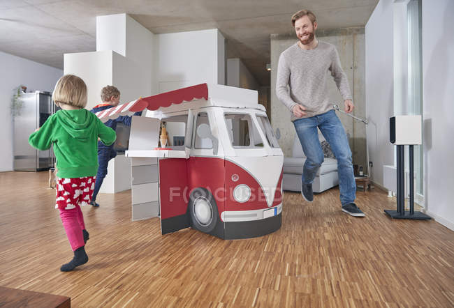 Happy father with children running around model car in living room — Stock Photo
