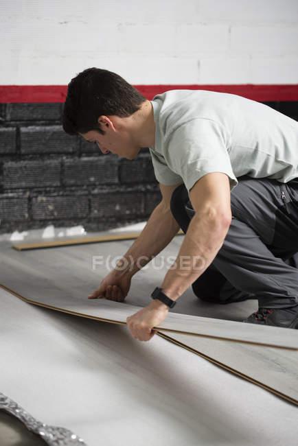 Jeune homme plaçant un plancher stratifié — Photo de stock