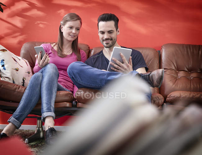 Young businessman and woman sitting on vintage couch using digital gadgets — Stock Photo