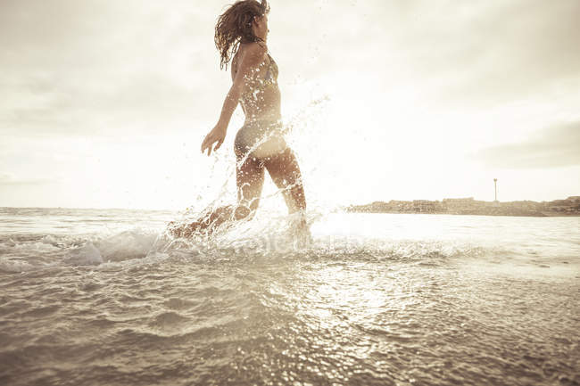 Spain, Tenerifa, young woman running into water against the sun — Stock Photo