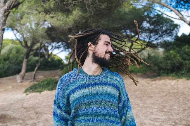 Young man with dreadlocks smiling and shaking his head — Stock Photo