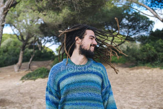 Молодой человек с дредами улыбается и качает головой — стоковое фото