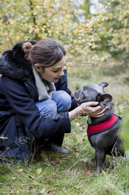 Femme accroupi avec chien mignon dans la nature — Photo de stock