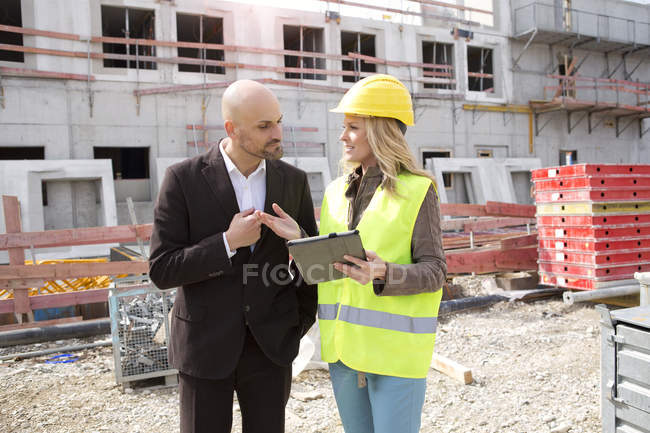 Woman with hard hat talking to man on construction site — Stock Photo
