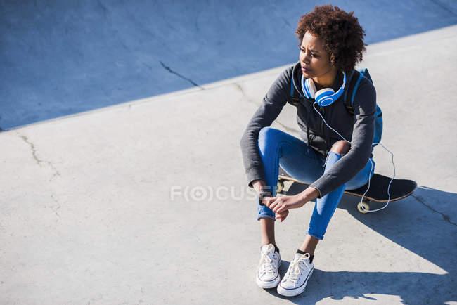 Молода жінка, сидячи на скейтборді — стокове фото