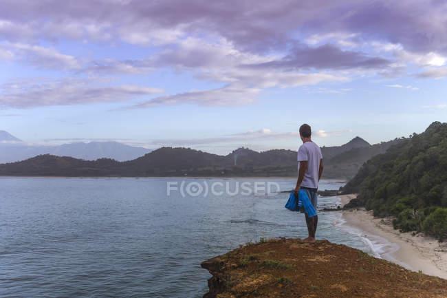 Indonesia, Isla de Sumbawa, Joven de pie en el mirador - foto de stock