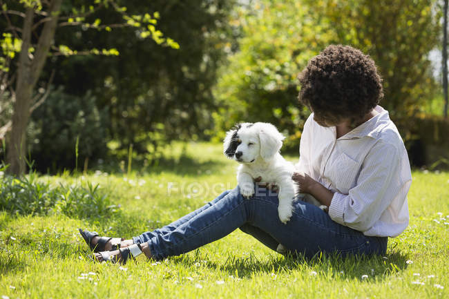 Woman sitting on meadow with dog — Stock Photo