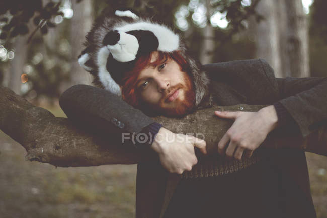 Portrait of redheaded young man wearing raccoon hat in woods — Stock Photo