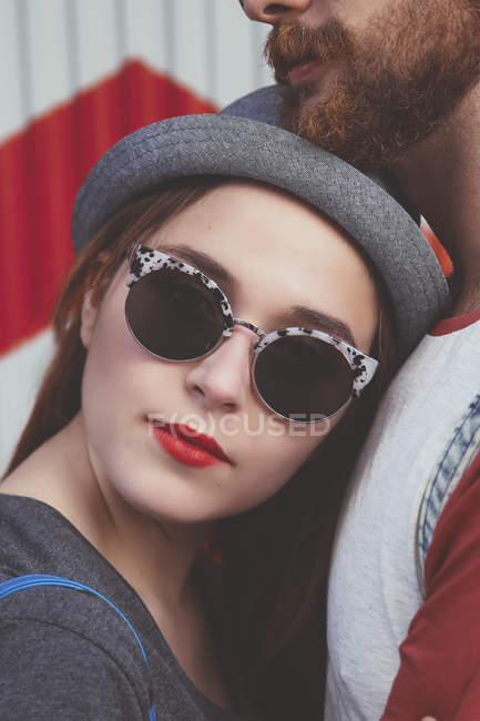 Portrait of young woman wearing sunglasses leaning agaich her boyfriend — Stock Photo