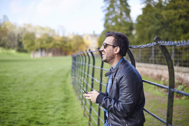 Сміх чоловіка з смартфон носити шкіряні куртки і сонцезахисні окуляри — стокове фото