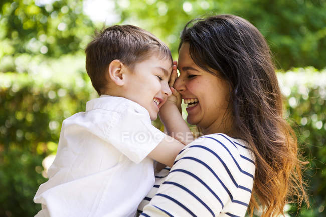 Happy mother and son hugging outdoors — Stock Photo