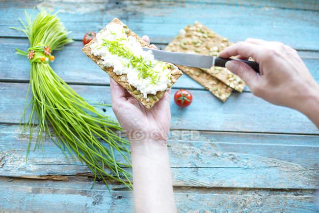 Руки разбрасывают сливочный сыр на хлеб — стоковое фото