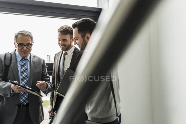 Три бизнесмена с цифровой планшет, говорить в лестница — стоковое фото