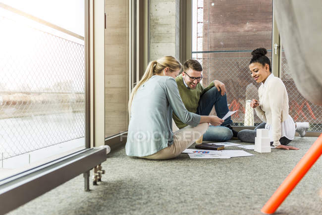 Three colleagues in office sitting on floor working together — Stock Photo