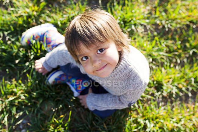 Retrato del niño sonriente sentado en el prado - foto de stock