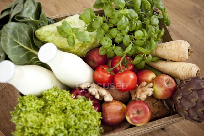 Деревянный ящик, свежие овощи и две бутылки молока — стоковое фото