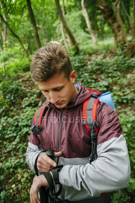 Young hiker looking at smartwatch at daytime — Stock Photo
