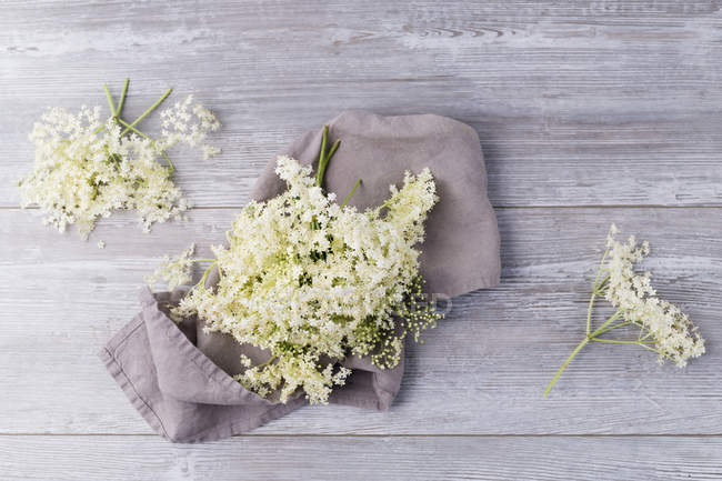 Closeup view of Elderflowers on cloth and wood — Stock Photo