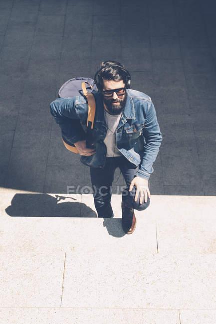 Молода людина з навушниками сходження великий сходи — стокове фото