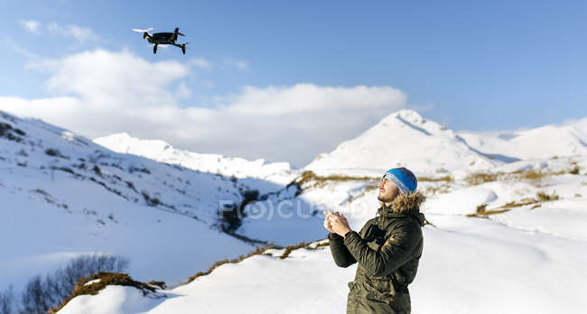 Man with flying drone in snowy mountains — Stock Photo