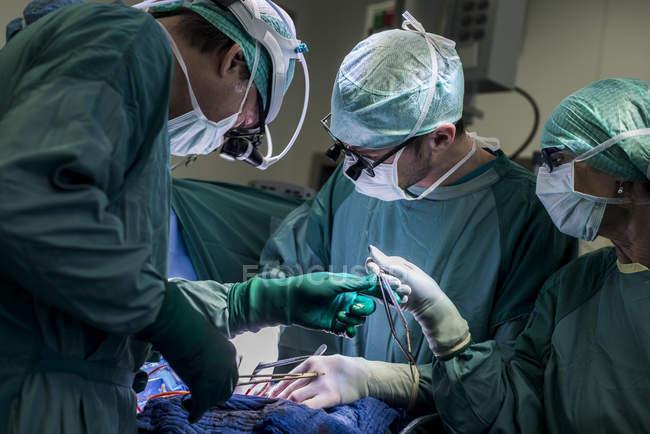 Кардиохирурги и операционная медсестра во время операции — стоковое фото