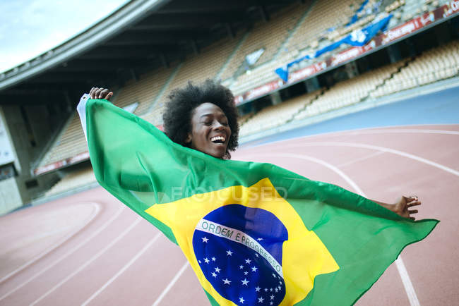 Young black athlete in stadium carrying Brazilian flag — Stock Photo