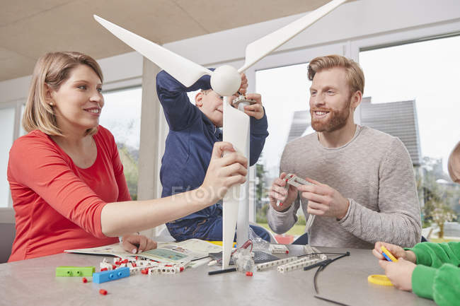 Family assembling toy wind turbine together — Stock Photo