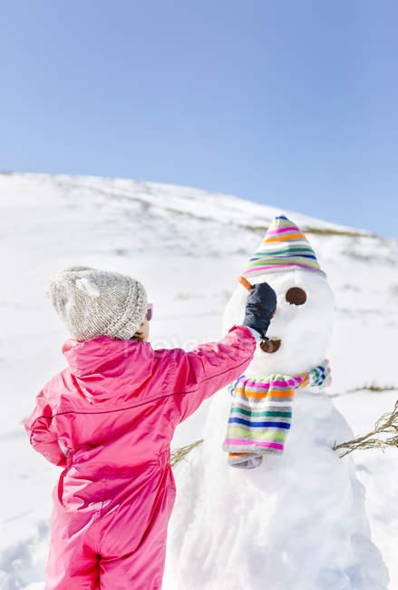 Vista posteriore della ragazza costruire pupazzi di neve neve in inverno — Foto stock