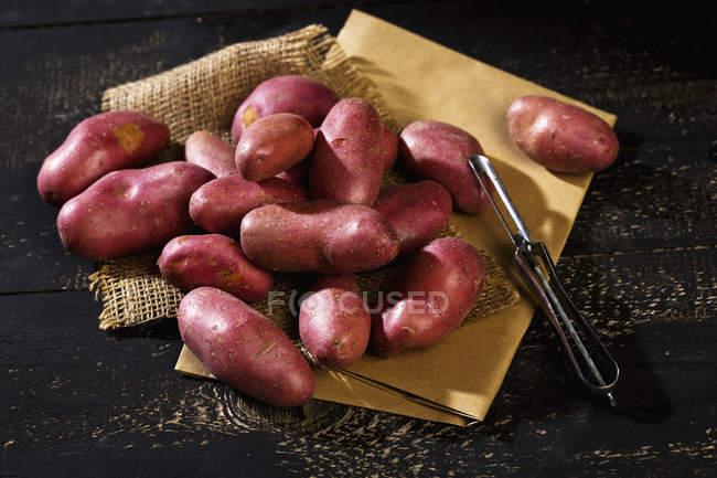 Raw Grenaille potatoes and peeler — Stock Photo