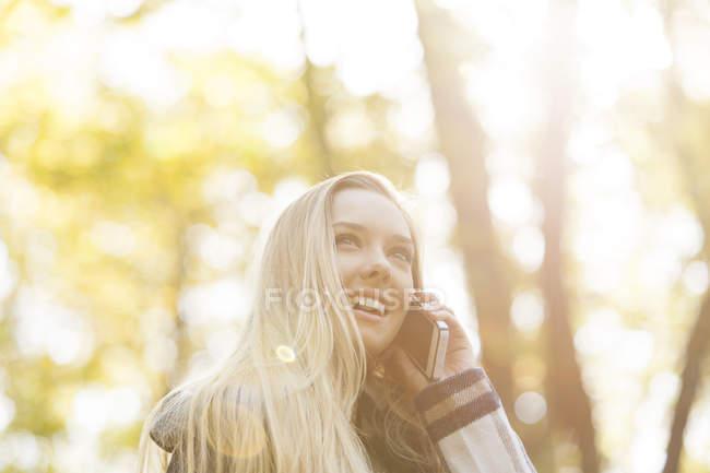 Улыбается девушка на мобильный телефон в осень — стоковое фото